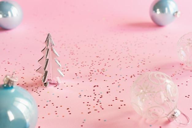 Kleine decoratieve kerstboom transparante en blauwe ballen en kleurrijke confetti op roze achtergrond