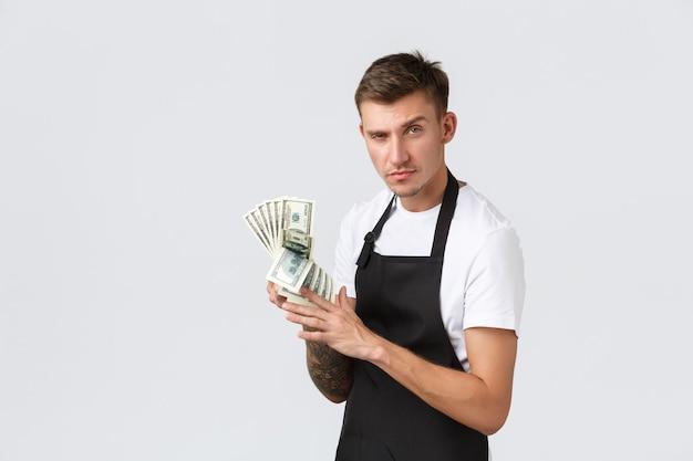 Kleine detailhandelsbetalingen en werknemersconcept brutale knappe verkoper café-eigenaar die telt...
