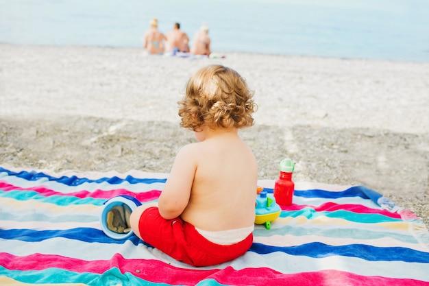 Kleine dikke jongen op het strand zit met zijn rug tegen de achtergrond van de zee