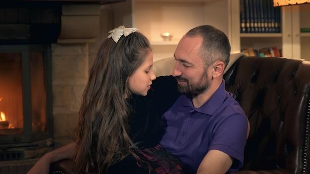 Kleine dochter die haar vader kietelt en hem bij de baard trekt