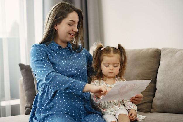 Kleine dochter met paardenstaarten. zwangere moeder in een jurk. dochter met een foto.
