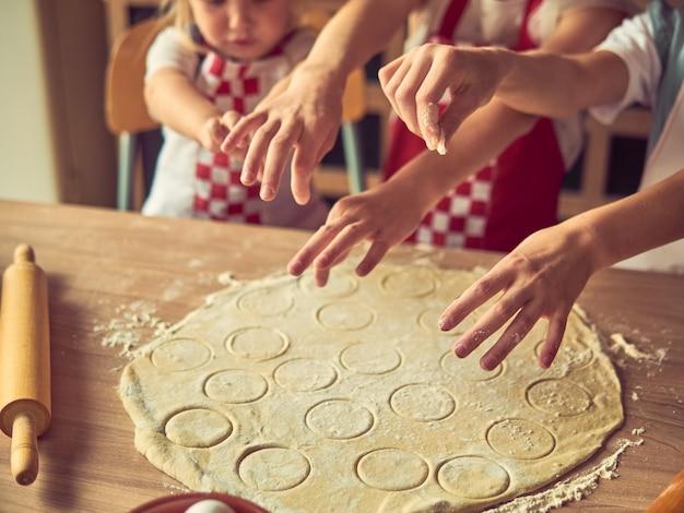 Kleine dochters die in keuken thuis allen samen koken. gelukkig gezin en levensstijl concept.
