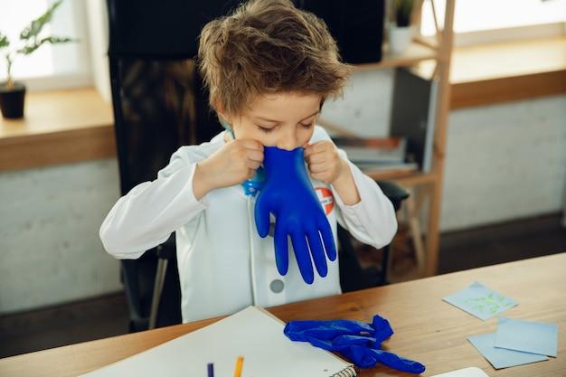 Kleine dokter tijdens grappig dragen van beschermende handschoenen.