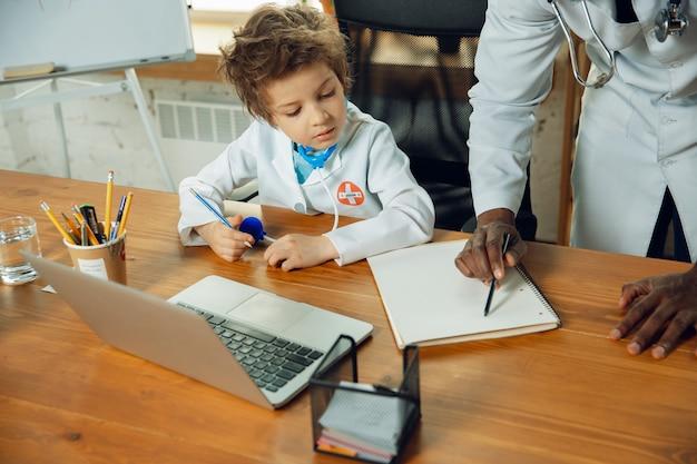 Kleine dokter tijdens het werken met oudere collega