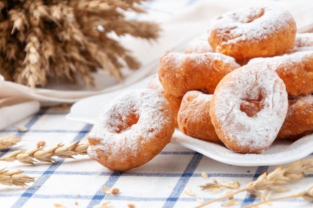 Kleine donuts bestrooid met poedersuiker. op een witte plaat. op de achtergrond tarweoren en granen.