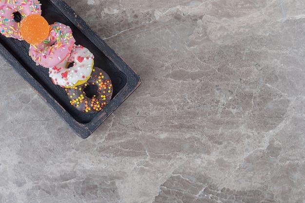 Kleine donuts en een marmelade gebundeld op een zwart dienblad op een marmeren oppervlak