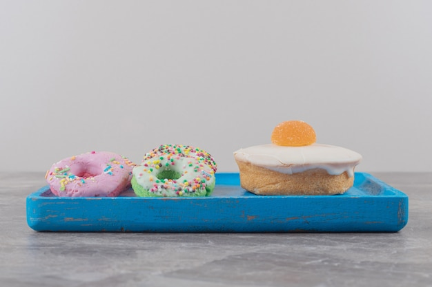 Kleine donuts en een witte chocoladetaart met marmelade op een dienblad op marmer