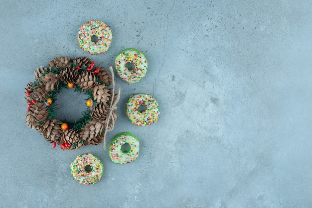 Kleine donuts rond een dennenappelkrans op marmer.