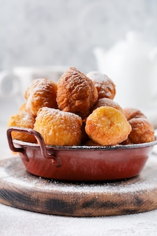 Kleine donuts. zelfgemaakte wrongel gebakken koekjes in diep vet en bestrooid met poedersuiker in een vintage bord