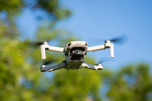 Kleine drone vliegt in de lucht met bomen aan de