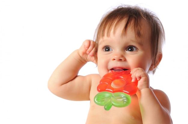 Kleine éénjarige baby houdt bij de hand kleurrijk bijtspeeltje. kindertanden barsten speelgoed uit. portret op geïsoleerd wit