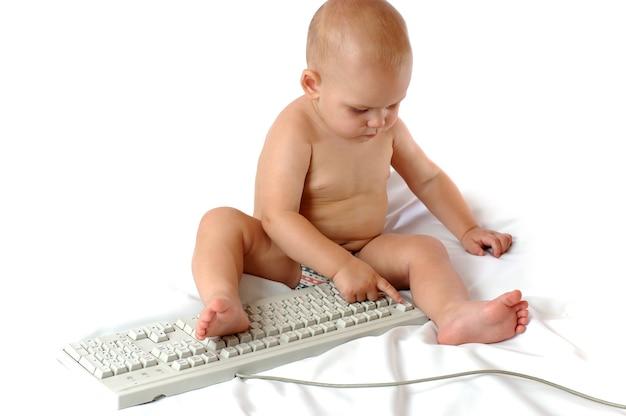 Kleine éénjarige jongen speelt met groot pc-toetsenbord op een afgelegen witte achtergrond