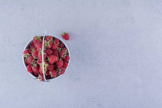 Kleine emmer gevuld met frambozen op marmeren achtergrond.
