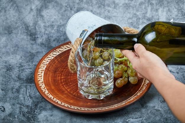 Kleine emmer met druiven in keramische plaat en hand gieten wijn in het glas op marmer.