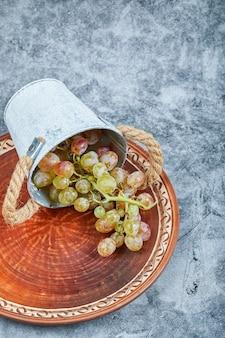 Kleine emmer met druiven in keramische plaat op een marmeren achtergrond. hoge kwaliteit foto