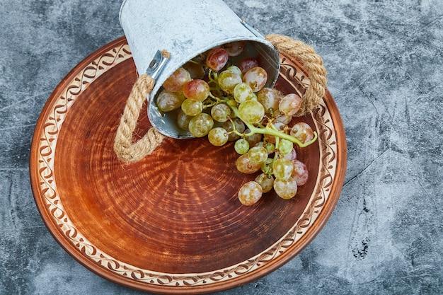 Kleine emmer met druiven in keramische plaat op marmer.