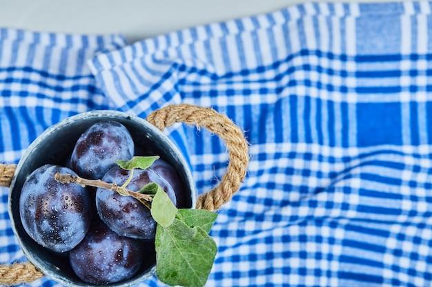 Kleine emmer tuinpruimen op blauw tafelkleed.