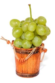 Kleine emmer vol met druiven geïsoleerd op de witte achtergrond