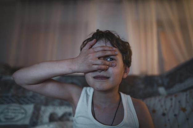 Kleine emotionele jongen bedekt zijn gezicht met zijn hand en kijkt naar een horrorfilm