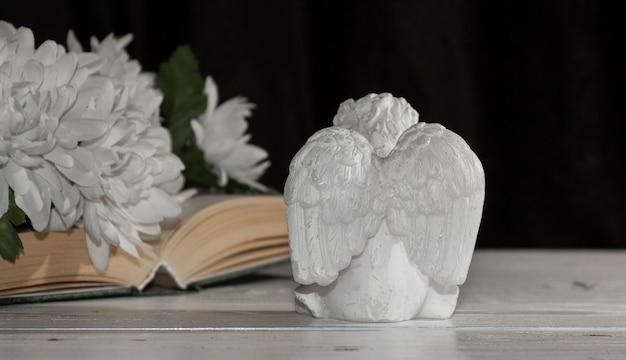 Kleine engel met vleugels op een zwarte achtergrond, bloemen en een boek, vrije ruimte voor tekst