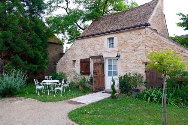 Kleine europese bakstenen landhuis binnenplaats met bestrating en gezellig terras in groene tuin met tuinmeubilair lounge groep met vintage metalen witte stoelen en tafel