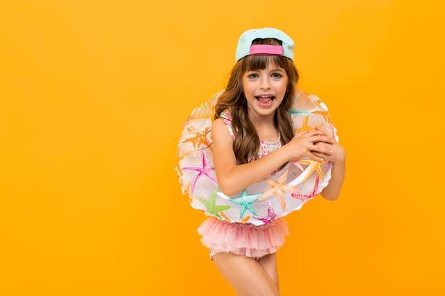 Kleine europese meisje met een baseballcap in een zwembroek met een cirkel zwemmen op een gele muur