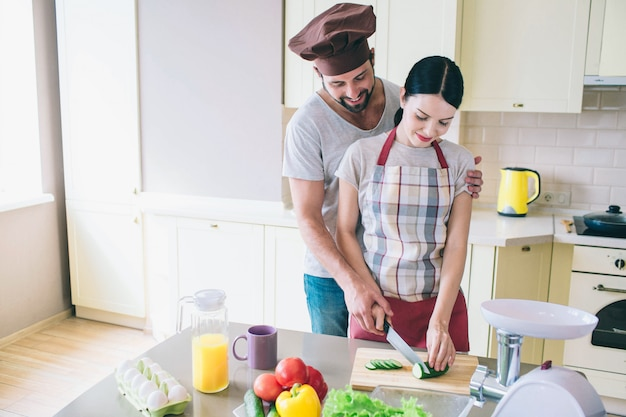 Kleine familie werkt samen in de keuken. man en vrouw samen gesneden komkommer.