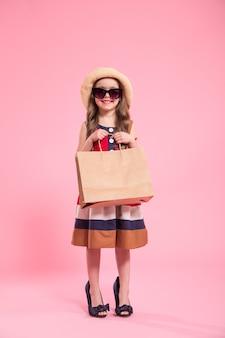 Kleine fashionista op een gekleurde achtergrond in mama's schoenen