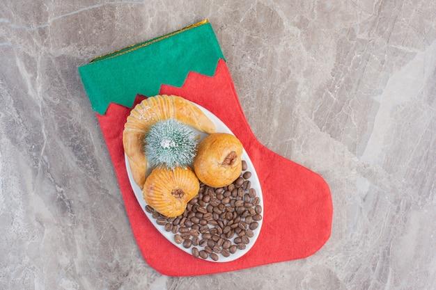 Kleine, feestelijke gebakjeschotel op een kerstsok op marmer.