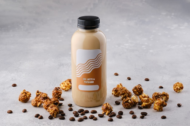 Kleine fles met ijs latte en popcorn cocktail op tafel