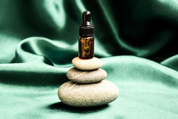 Kleine fles serum op stapel basaltstenen op groene satijnen stof achtergrond. trendy kleur. beauty pipet druppelaar op piramide van kiezelstenen. natuurlijke geneeskunde, neusdruppels, oogdruppels