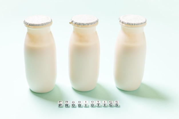 Kleine flesjes met probiotica en prebiotica zuiveldrank op blauwe achtergrond