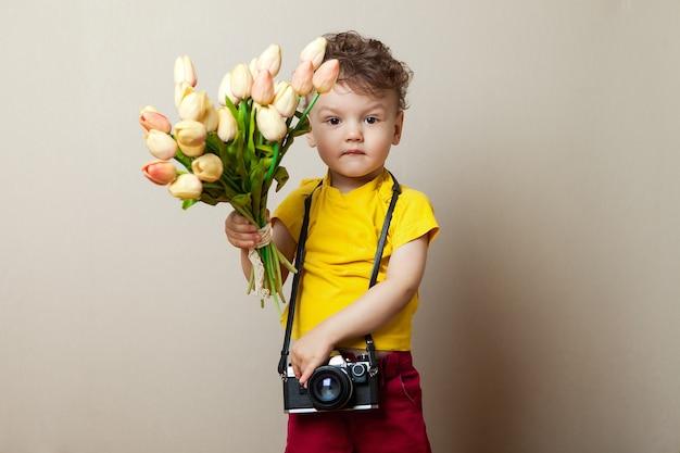 Kleine fotograaf, een kind met een camera in hun handen en bloemen. boeket tulpen voor moederdag.
