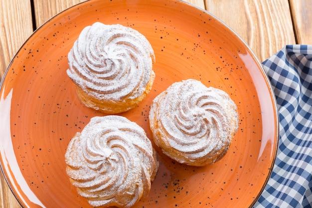 Kleine franse koekjes profitroles met suikerpoeder close-up