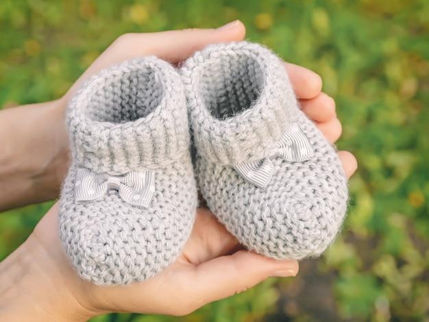 Kleine gebreide slofjes voor pasgeborenen in de palm van je hand op onscherpe achtergrond, concept van wachten op het eerste kind in het gezin