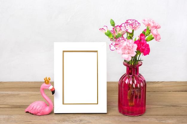 Kleine gekleurde roze anjers in vaas, witte fotolijst, figuur van flamingo op houten tafel en grijze muur