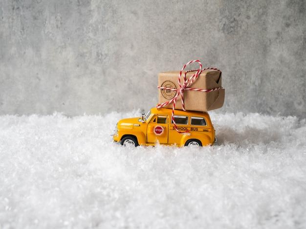 Kleine gele speelgoed schoolbus draagt een kerst- of nieuwjaarscadeau op het dak