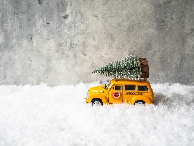 Kleine gele speelgoed schoolbus draagt een kerstboom op het dak