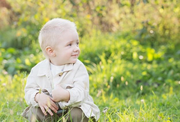 Kleine gelukkige blonde jongen buiten op zonnige zomerdag