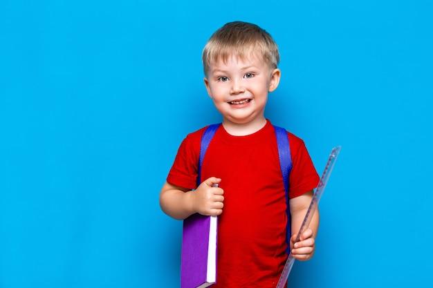 Kleine gelukkige glimlachende jongen met een bril op zijn hoofd, boek in handen, schooltas op zijn schouders. terug naar school. klaar om naar school te gaan