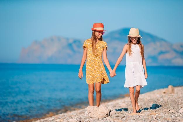 Kleine gelukkige grappige meisjes hebben veel plezier op tropisch strand samen spelen