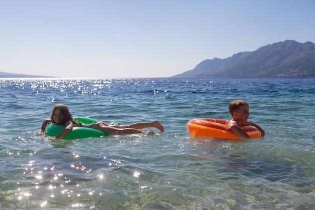 Kleine gelukkige jongen en meisje drijvend in de zee op een opblaasbare ring, concept van kinder- en familie zomervakantie