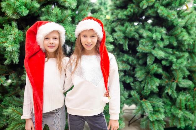 Kleine gelukkige meisjes dichtbij sparrentak in sneeuw voor nieuw jaar.