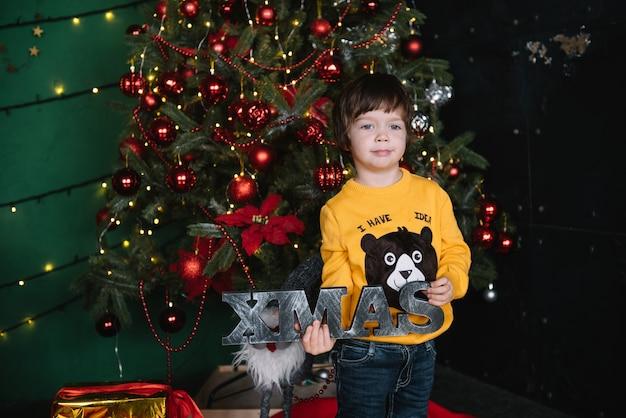 Kleine gelukkige schattige jongen in de buurt van de kerstboom en heeft een geschenkdoos. kind. kerststemming. vakantie. kerstmis. nieuwjaar.