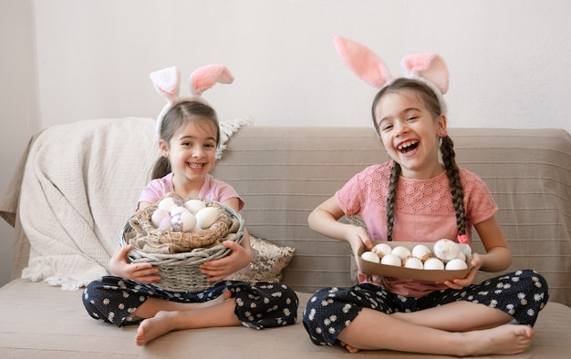 Kleine gelukkige zusjes met konijnenoren, met paaseieren