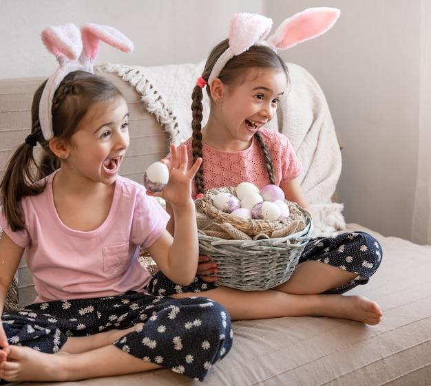Kleine gelukkige zusjes met konijnenoren poseren met een mandje met paaseieren