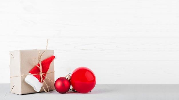 Kleine geschenkdoos met kerstballen op tafel