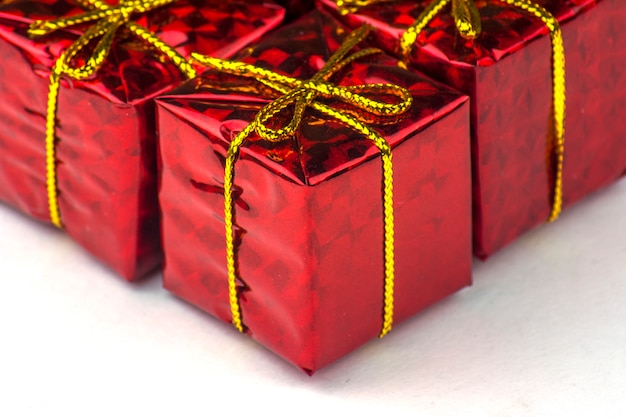 Kleine geschenken verpakt in rood glanzend papier. rode geschenkdozen close-up op witte achtergrond