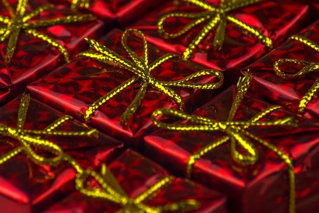 Kleine geschenken verpakt in rood glanzend papier. rode geschenkdozen close-up