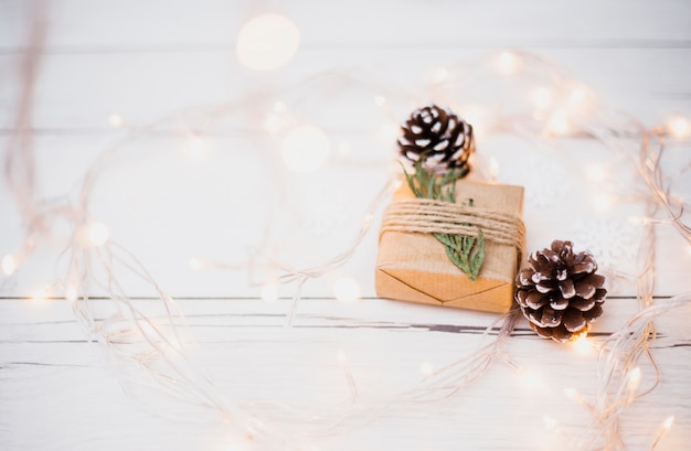 Kleine geschenkverpakking in de buurt van winkelhaken en verlichte kerstverlichting